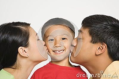 Parents kissing boy.