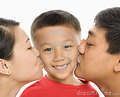 Parents kissing son.