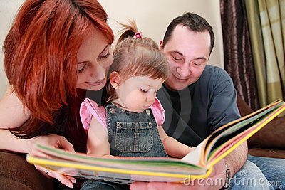 Parents and little daughter reads book