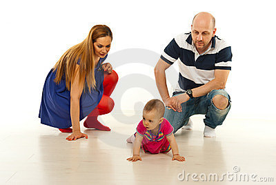 Parents looking at baby crawling