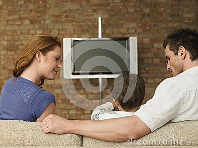 Parents Looking At Boy Watching TV At Home