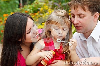 Parents observe as daughter blows soap bubble
