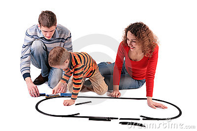Parents play with son in toy railroad