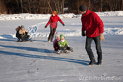 Parents pull children on sleds