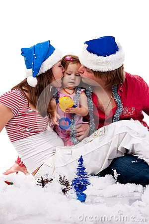 Parents in Santa s hat kissing their child