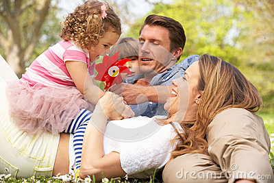 Parents Sitting With Children In Field