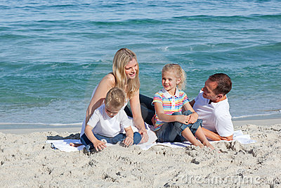 Parents with their children sitting on the sand