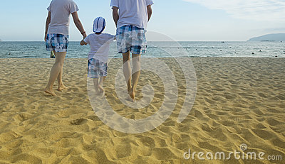 Parents walking with child on the beach