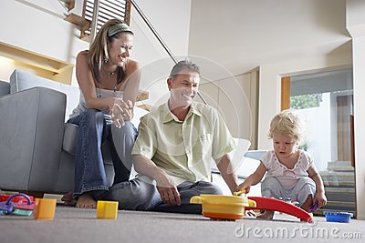 Parents Watching Son Playing With Toy