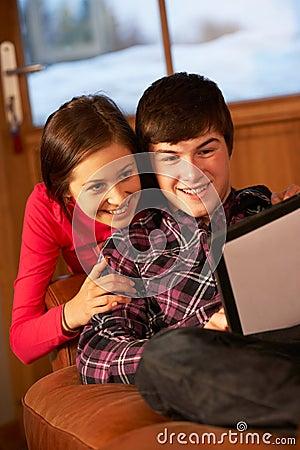 Pares adolescentes que relaxam com computador da tabuleta