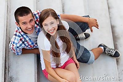 Pares adolescentes que se sientan en las escaleras