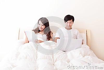 Pares alegres usando a almofada de toque na cama