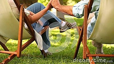 Pares aposentados que sentam-se nas cadeiras de plataforma que guardam as mãos vídeos de arquivo