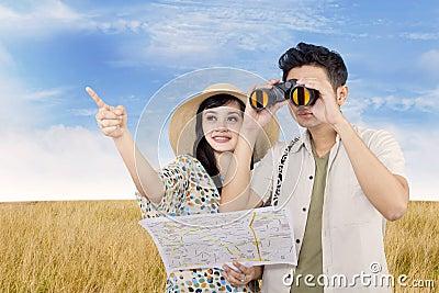 Pares asiáticos usando binóculos no campo