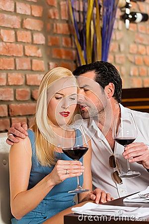 Pares atractivos que beben el vino rojo en restaurante