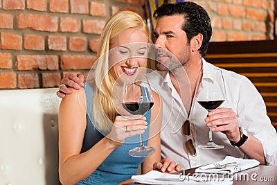 Pares atrativos que bebem o vinho vermelho no restaurante