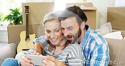 Pares bonitos que sentam-se contra um cartão que toma um selfie filme