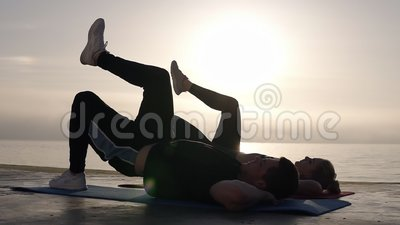 Pares caucasianos novos aptos que dão certo junto no beira-mar da manhã A mulher e o homem do ajuste que fazem a imprensa levanta filme