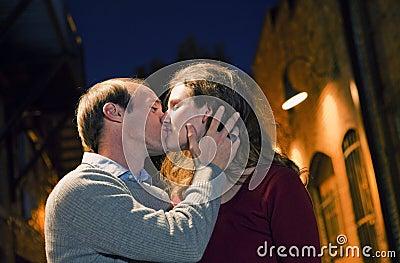 Pares caucasianos que beijam na maneira da aléia do tijolo