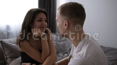 Pares de amor felizes que relaxam na cama em casa, homem novo que toca nos pés bonitos de sorriso da mulher, olhando nos olhos vídeos de arquivo
