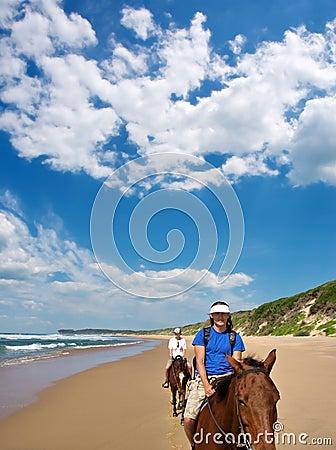 Pares de cavaleiros na praia sob céus dramáticos