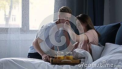 Pares de sorriso que comem o café da manhã na cama na manhã video estoque