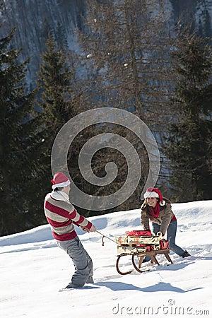 Pares do Natal que jogam com os presentes na neve