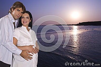 Pares embarazados felices en la playa en la salida del sol