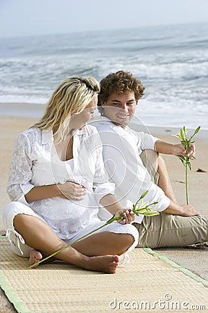 Pares embarazados jovenes felices que se relajan en la playa