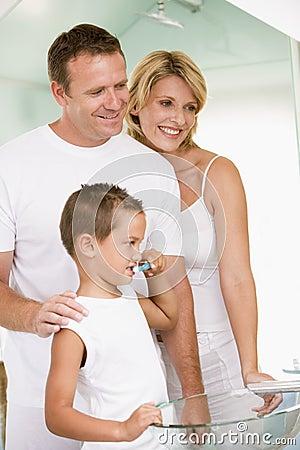 Pares en cuarto de baño con los dientes que aplican con brocha del muchacho joven