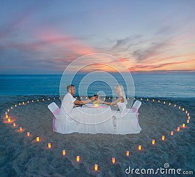 Pares en la cena rom ntica de la playa con el coraz n de las velas foto de archivo libre de - Cena romantica con velas ...