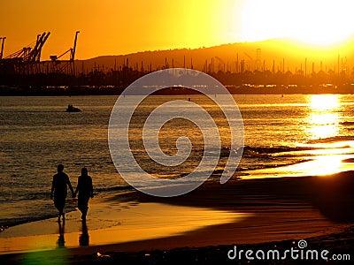 Pares en la playa en la puesta del sol