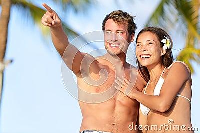 Pares en la playa feliz en traje de baño, el señalar del hombre