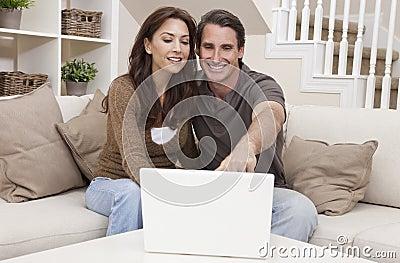 Pares felices del hombre y de la mujer usando el ordenador portátil