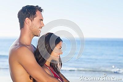 Pares felices en el traje de baño que abraza mientras que mira el agua