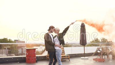 Pares felices jovenes que caminan en el tejado con la bomba de humo amarilla por el edificio moderno en la puesta del sol outdoor almacen de video