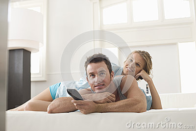 Pares felices que ven la TV en casa
