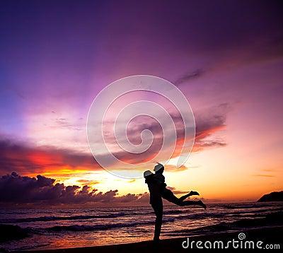 Pares felizes que abraçam na praia