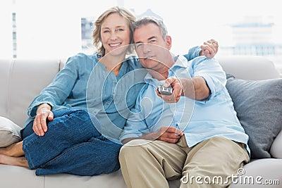 Pares felizes que afagam e que sentam-se no sofá que olha a tevê
