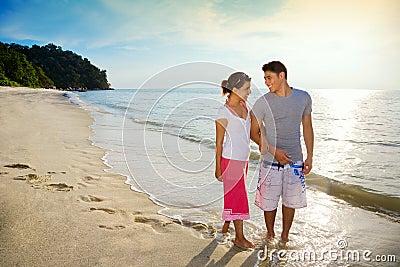 Pares felizes que andam ao longo da praia