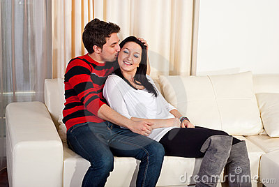 Pares jovenes cariñosos en hogar del sofá