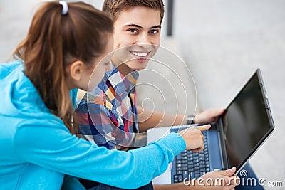 Pares jovenes con la computadora portátil