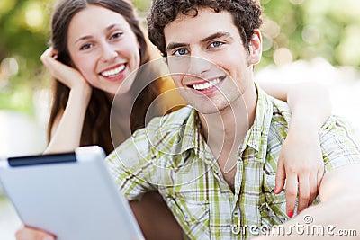 Pares jovenes con la tableta digital
