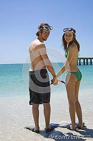 Pares jovenes en tubo respirador de la playa