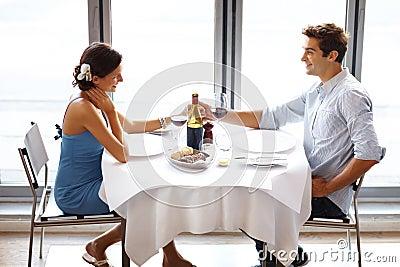 Pares jovenes felices el fecha en restaurante