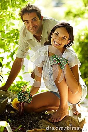 Pares jovenes felices que cultivan un huerto al aire libre sonriendo