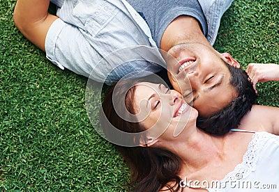 Pares jovenes felices que se reclinan en el parque