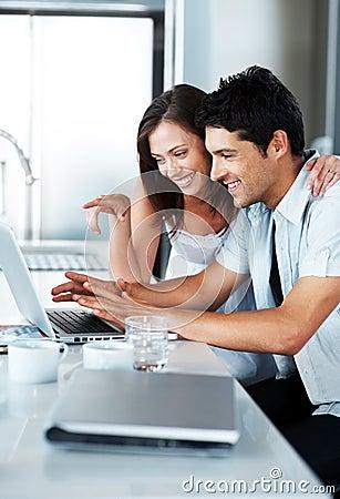 Pares jovenes hermosos usando la computadora portátil junto