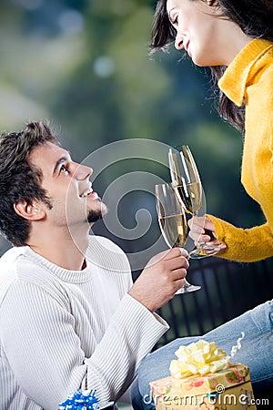 Pares jovenes que celebran acontecimiento con los vidrios y los regalos del champán