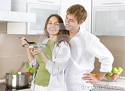 Pares jovenes que cocinan junto